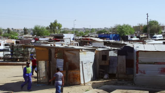WS People walking passed corrugated iron shacks in town / Diepsloot, South Africa