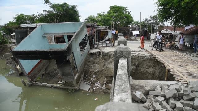 august people walking past a house which was destroyed by a landslide after heavy monsoon rain in a flood affected village in barpeta district of... - demolished stock videos & royalty-free footage