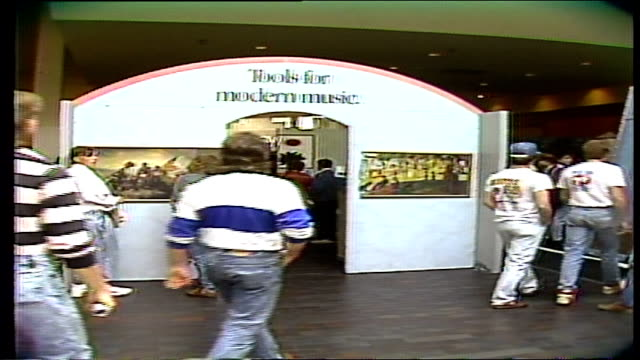 people walking past and into a tools for modern music arch and display - mtv1 stock-videos und b-roll-filmmaterial