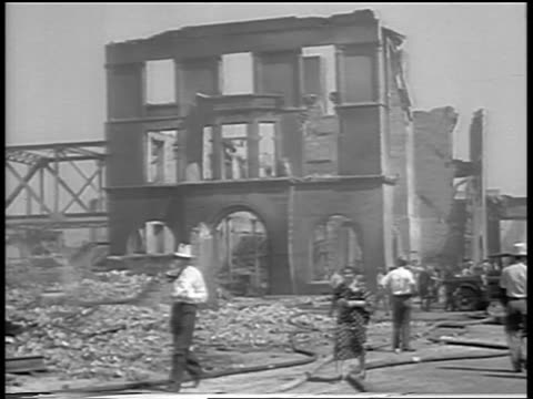 b/w 1934 people walking past burned buildings after chicago stockyard fire / newsreel - anno 1934 video stock e b–roll