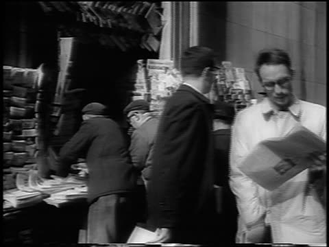 stockvideo's en b-roll-footage met b/w 1963 people walking past + buying newspapers from newsstand / man reading paper / nyc - 1963