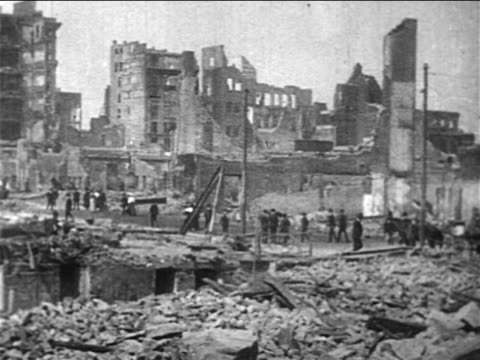 pan people walking past destroyed buildings after san francisco earthquake / documentary - anno 1906 video stock e b–roll