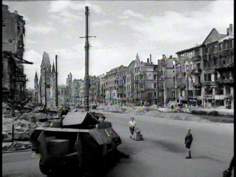 vidéos et rushes de people walking past devastated buildings and burned out tank destroyer on street of postwar berlin / germany - 1945
