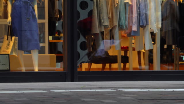 stockvideo's en b-roll-footage met mensen lopen langs fashion store - etalage