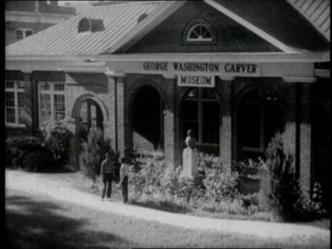 1940 People walking past George Washington Carver Museum / Tuskegee, Alabama, United States