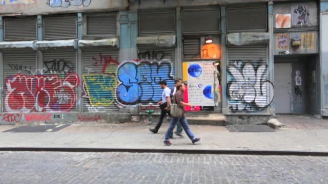 People walking past graffiti in Greewich Village