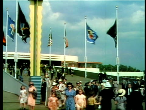 people walking past international flags at new york world's fair / industrial - fade in stock videos & royalty-free footage