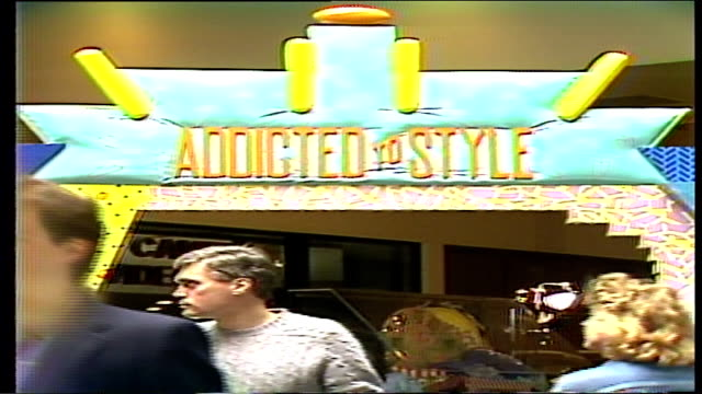 people walking past large addicted to style display arch - mtv1 stock-videos und b-roll-filmmaterial