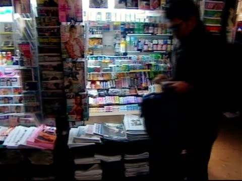 vidéos et rushes de people walking past newsstand in times square at night / new york city - kiosque à journaux