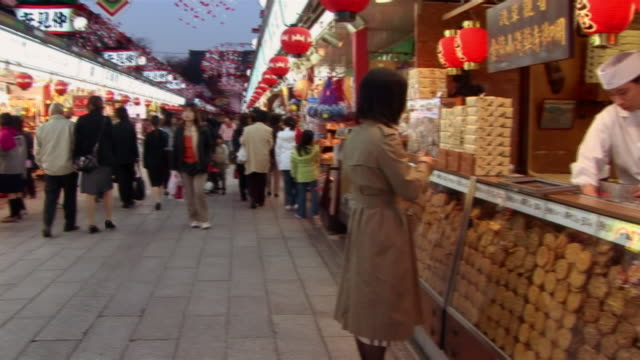 People walking past souvenir stalls on Nakamise Street / pan to woman buying cookies from cookie vendor / Tokyo