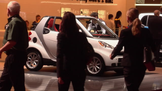 WS People walking past the Smart 'For Two' display at Detroit Auto Show/ Detroit, Michigan