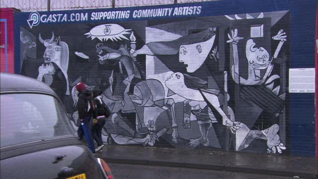 People walking past wall art in Belfast, Northern Ireland