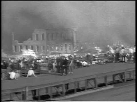 people walking past + watching fire in chicago stockyard / newsreel - 1934 個影片檔及 b 捲影像