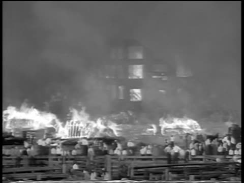 b/w 1934 people walking past watching fire in chicago stockyard / newsreel - 1934 stock videos and b-roll footage
