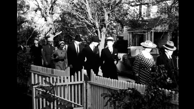 stockvideo's en b-roll-footage met people walking past white picket fence along treelined street people walking past white picket fence on january 01 1940 - tuinhek
