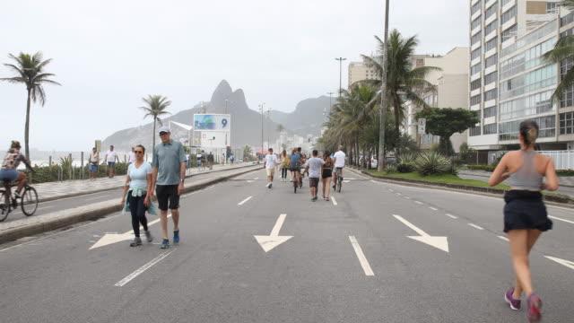 vídeos de stock, filmes e b-roll de people walking riding scooters and jogging on november 24 2019 in rio de janeiro brazil every sunday in ipanema a road lane is closed for pedestrians... - artigo de decoração