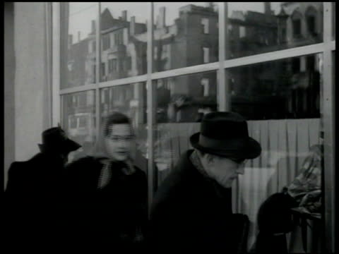 people walking sidewalk in front of ulwa store man looking in department store window woman modeling cape dress hat to seated uniformed us service... - 1947 stock-videos und b-roll-filmmaterial