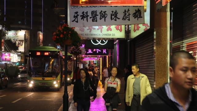 people walking the busy avenida de lisboa towards the camera at night tourism and gambling are the primary drivers of macau's economy - avenida stock videos & royalty-free footage