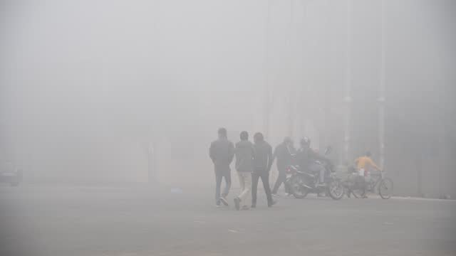 people walking through dense fog in a street, on a cold winter morning in new delhi, january. 1, 2021. delhi recorded the season's lowest temperature... - human interest stock videos & royalty-free footage