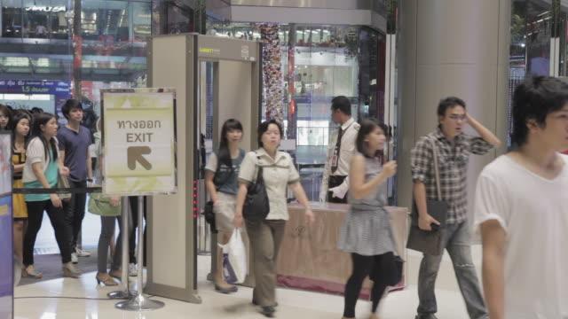 ws people walking through metal detector at mall / bangkok, thailand - metal detector sicurezza video stock e b–roll