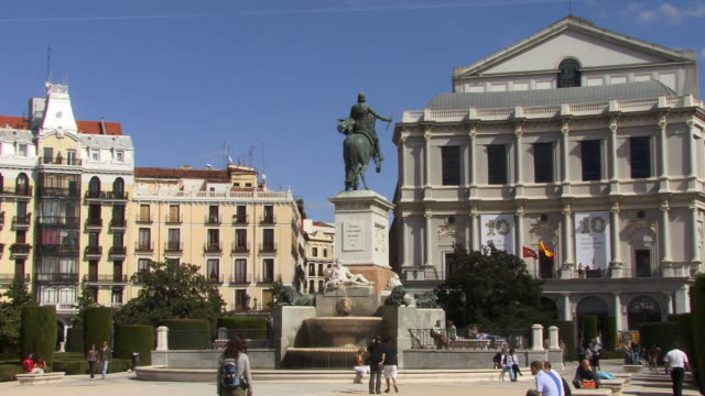 ws zo people walking through plaza de oriente, past opera house and statue of king philip iv  - male likeness stock videos & royalty-free footage