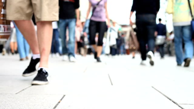 people walking through the city defocused - zona pedonale strada transitabile video stock e b–roll