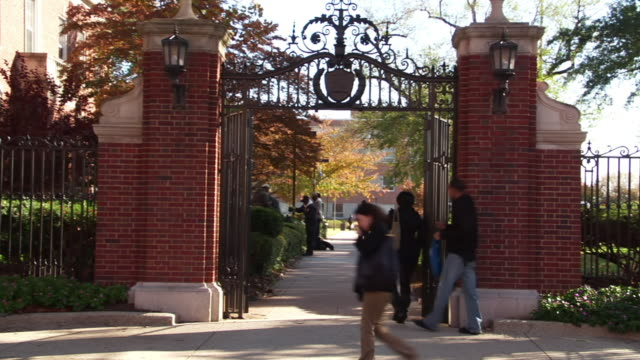 WS People walking through wrought iron gate on Howard University campus / Washington, District of Columbia, United States