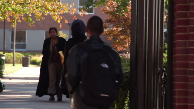 MS People walking through wrought iron gate on Howard University campus / Washington, District of Columbia, United States