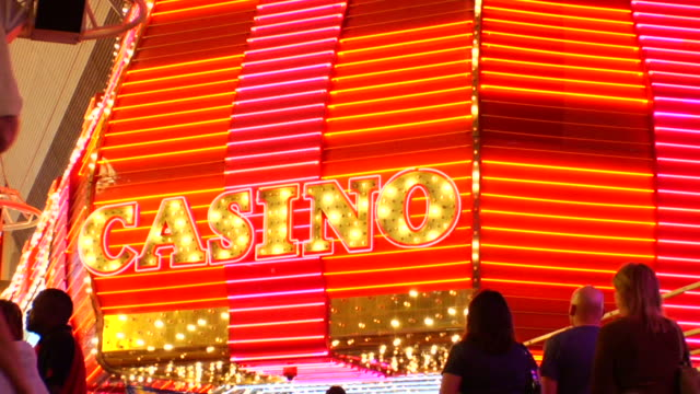 people walking toward casino sign w/ letters in light bulbs bright neon bars of traveling lights gambling wagering night life lifestyle glitz glitter... - casino lights stock videos & royalty-free footage