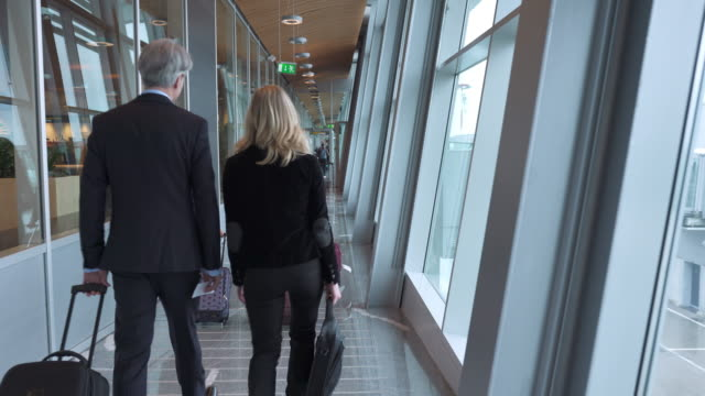 people walking toward departure gates on airport - gate stock videos & royalty-free footage