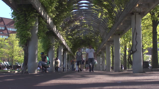 People walking under covered trellis in Christopher Columbus Park.