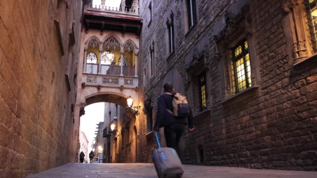people walking under the pont del bisbe, or bishop's bridge in barcelona's gothic quarter - ゴシック地区点の映像素材/bロール