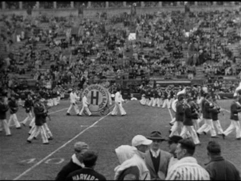 vídeos de stock, filmes e b-roll de people walking up harvard stadium ramp steps ws harvard university band marching on field crimson players jogging out of gate into field college... - 1951