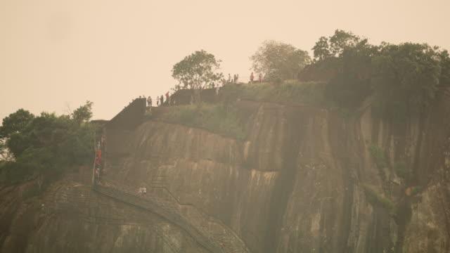 vídeos de stock e filmes b-roll de ms people walking up steps along sunny cliff,sri lanka - focagem difusa