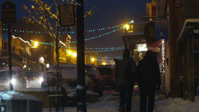 people walking up the streets of park city at night - park city utah video stock e b–roll