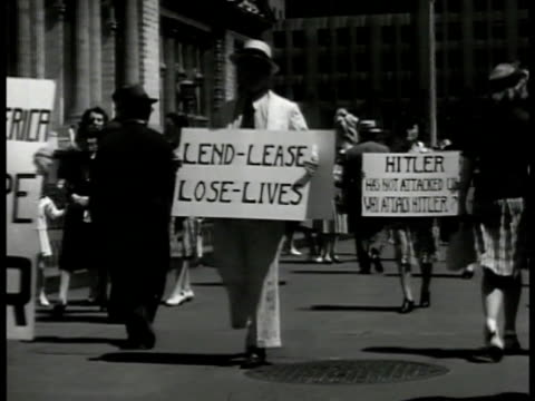 vidéos et rushes de people walking w/ signs picketing war involvement on sidewalk signs 'stay out' 'lend lease loose lives' 'europe for europeans america for americans'... - 1941