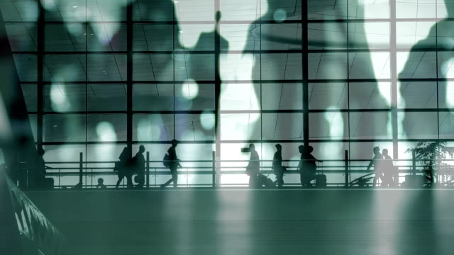people walking with luggage at a modern station - controluce video stock e b–roll