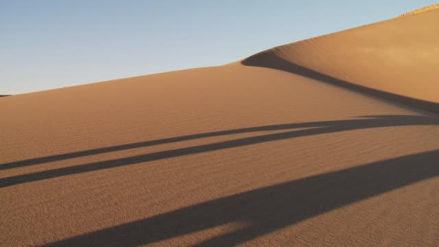 ws people walking with sandboarders in sand dune with shadows / san pedro de atacama, norte grande, chile  - fußabdruck stock-videos und b-roll-filmmaterial