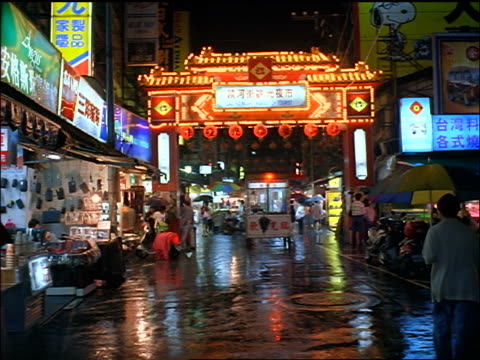 people walking with umbrellas on wet street by outdoor market / night market, taipei, taiwan - taiwan stock videos and b-roll footage
