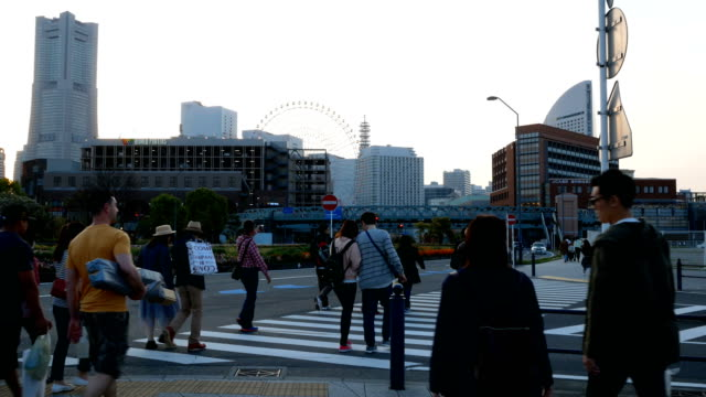 people walks across the street in yokohama, japan - crosswalk sign stock videos & royalty-free footage