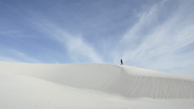 vidéos et rushes de people walks on desert dunes, wide - au loin