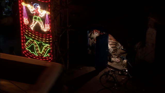 vídeos de stock, filmes e b-roll de people wander about streets below brightly coloured lights during diwali festival of light available in hd. - festival tradicional
