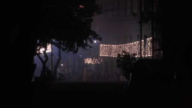 vídeos de stock, filmes e b-roll de people wander streets as fireworks explode for diwali hindu festival of lights available in hd. - festival tradicional
