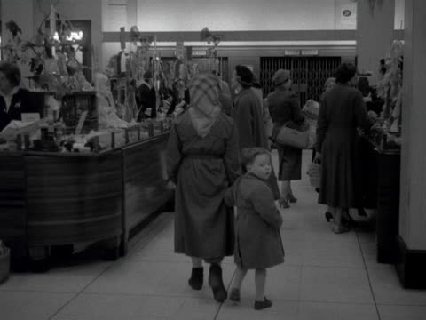 people wander through a department store as the camera pans to a stand selling scarves. 1957. - department store stock videos & royalty-free footage