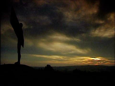 people wandering past angel of the north as sun sets gateshead - gateshead stock videos and b-roll footage