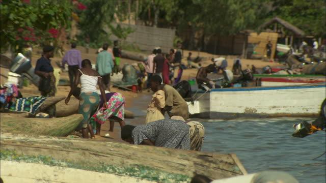 vídeos de stock e filmes b-roll de people wash clothes on the shoreline of lake malawi. - malávi
