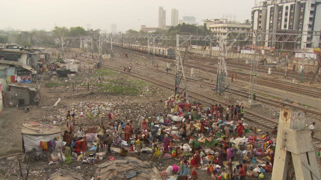 WS HA People washing clothes in slum area near train station / Mumbai, India
