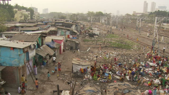 ws ha people washing clothes in slum area near train station / mumbai, india - slum stock-videos und b-roll-filmmaterial