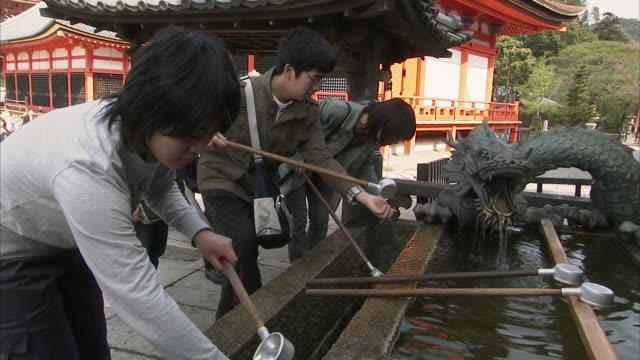 vídeos y material grabado en eventos de stock de ms people washing hands in tsukubai at kiyomizu-dera temple, kyoto, japan - encuadre de tres cuartos