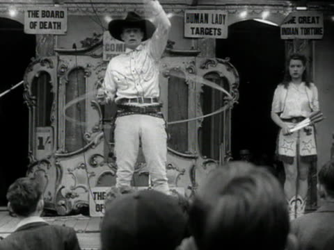 People watch a cowboy performing a rope trick at a fairground on Hampstead Heath